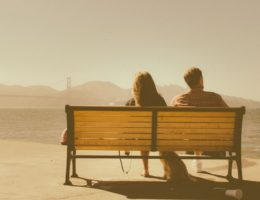 couple sitting on bench not defining their relationship